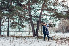Beautiful loving couple walking in winter forest together. People hugging outdoors. Beautiful loving couple walking in winter forest together. Happy people royalty free stock image