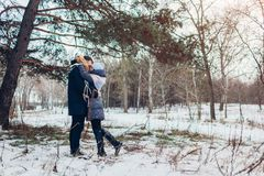 Beautiful loving couple walking in winter forest together. People hugging outdoors. Beautiful loving couple walking in winter forest together. Happy people stock photography