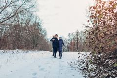 Beautiful loving couple walking in winter forest together. People having fun outdoors. Beautiful loving couple walking in winter forest together. Happy people royalty free stock photography