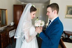 Beautiful loving wedding couple is holding flowers bouquet and kissing at luxury hotel interior background Stock Images