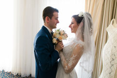 Beautiful loving wedding couple is holding flowers bouquet and kissing at luxury hotel interior background Stock Image