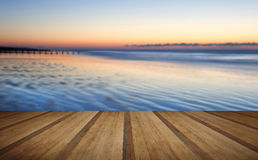 Beautiful low tide beach vibrant sunrise with wooden planks floo Royalty Free Stock Photography