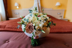 Beautiful lush wedding bouquet on bed in bride`s bedroom. Beautiful lush wedding bouquet on a bed in a bride`s bedroom Stock Photo