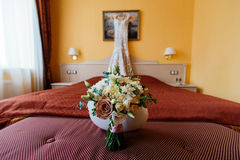 Beautiful lush wedding bouquet on a bed in a bride`s bedroom. With blured wedding dress in the background Royalty Free Stock Photo
