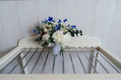 Beautiful lush wedding bouquet white peonies and blue flowers in room Stock Photography