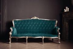 Luxurious antique velor sofa turquoise color near the fireplace. Beautiful luxurious antique velor sofa turquoise color near the fireplace Stock Photos
