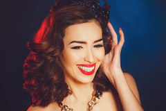 Beautiful luxurious princess in the diadem. Beautiful woman - brunette with long curly hair, bright makeup and dark-colored crown on his head, wearing a large royalty free stock photos