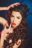 Beautiful luxurious princess in the diadem. Beautiful woman - brunette with long curly hair, bright makeup and dark-colored crown on his head, wearing a large royalty free stock photo