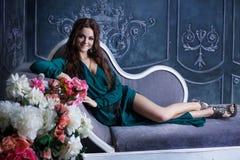 Beautiful luxurious woman in  green dress sitting Stock Photo