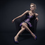 Beautiful luxurious woman sitting on chair. Royalty Free Stock Photography