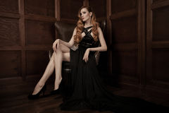 Beautiful luxurious woman sitting on a leather vintage chair Royalty Free Stock Image