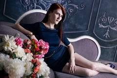 Beautiful luxurious woman sitting on a vintage Royalty Free Stock Images