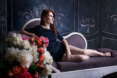 Beautiful luxurious woman sitting on a vintage Stock Images