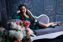 Beautiful luxurious woman sitting on a vintage Royalty Free Stock Image