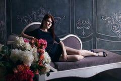 Beautiful luxurious woman sitting on a vintage Stock Photo