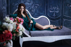 Beautiful luxurious woman sitting on a vintage Royalty Free Stock Photography