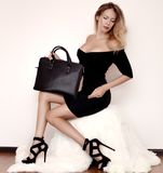 Beautiful luxurious young woman in a black dress sits on a white fur cover in black fashionable sandals and a handbag. In light room stock image