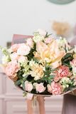 Beautiful luxury bouquet of mixed flowers in woman hand. the work of the florist at a flower shop. Cute lovely girl Royalty Free Stock Image