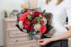 Beautiful luxury bouquet of mixed flowers in woman hand. the work of the florist at a flower shop. A small family. Business stock photo