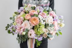 Beautiful luxury bouquet of mixed flowers in woman hand. the work of the florist at a flower shop. A small family. Business royalty free stock image