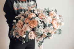 Beautiful luxury bouquet of mixed flowers in woman hand. the work of the florist at a flower shop. A small family. Business stock images
