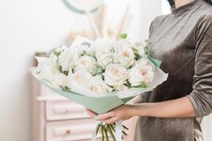 Beautiful luxury bouquet of white rose in woman hand. the work of the florist at a flower shop. David Austin. Beautiful luxury bouquet of white rose in woman Royalty Free Stock Photo