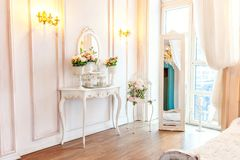 Beautiful luxury classic white bright clean interior bedroom in baroque style with mirror, table, large window, and flower royalty free stock photos