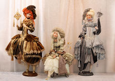Beautiful luxury dolls ladies at the masquerade. Three beautiful court ladies (handmade dolls with porcelain face) in medieval luxury dresses and accessories at Royalty Free Stock Photography