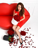 Beautiful luxury fashionable woman legs in high hills and red dr. Ess with roses bouquet and petals Royalty Free Stock Photography