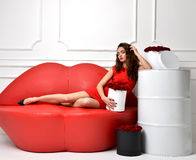 Beautiful luxury fashionable woman lying on red lips sofa couch Stock Photography