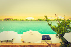 Beautiful luxury hotel swimming pool resort. With umbrella and chair on the beach and sea - Vintage Filter and Boost up color Processing Royalty Free Stock Photo