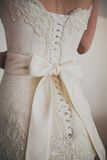 Beautiful luxury lace wedding dress and white bow Stock Photography