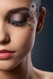 Beautiful luxury makeup with strasses. Partial facial portrait of beautiful woman wearing luxury makeup with strasses, closed eyes Stock Photo