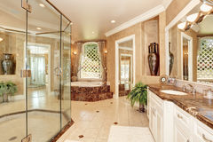 Beautiful luxury marble bathroom interior in beige color. Great bathtub with steps and large glass walk in shower. Northwest, USA Royalty Free Stock Images