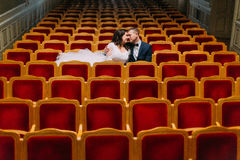 Beautiful luxury newlyweds kissing in small vintage theathre Stock Photo