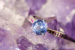 Beautiful luxury ring on Ametyst. Closeup of a Ring of Sapphire and Ruby on Ametyst Royalty Free Stock Photo