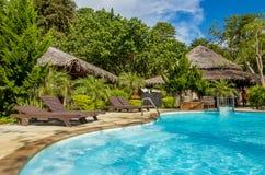 Beautiful luxury swimming pool by exotic beach Stock Image