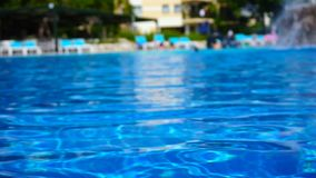 Beautiful luxury swimming pool in hotel resort with silhouette man and women. Around pool with sunshine and water reflection stock footage