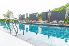 Beautiful luxury umbrella and chair around outdoor swimming pool Stock Photos