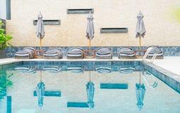 Beautiful luxury umbrella and chair around outdoor swimming pool Stock Photo