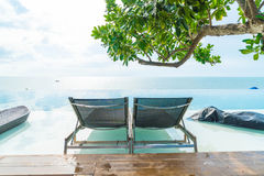Beautiful luxury umbrella and chair around outdoor swimming pool Stock Images