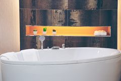 Beautiful luxury vintage empty bathtub Freestanding white bath. Bathroom is beautifully decorated with wooden tiles and electric lamps stock image