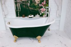 Beautiful luxury vintage empty bathtub near big window in bathroom interio, free space. Freestanding white bath. The bathroom is beautifully decorated with stock photography