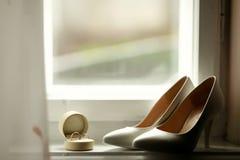 Beautiful luxury wedding rings and bride heels Stock Photos