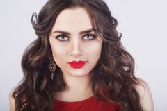 Beautiful luxury woman with jewelry, earrings. Beauty and accessories. Sexy brunette girl with big red lips in a red dress. Fashion model with long curly hair Stock Image