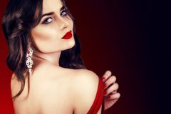 Beautiful luxury woman with jewelry, earrings. Beauty and accessories. Sexy brunette girl with big red lips in a red dress. Fashion model with long curly hair Royalty Free Stock Photos