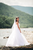 Beautiful luxury young bride in long white wedding dress and veil standing near river with mountains on background Royalty Free Stock Photos