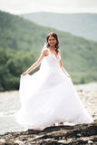 Beautiful luxury young bride in long white wedding dress and veil standing near river with mountains on background Royalty Free Stock Image