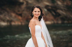 Beautiful luxury young bride in long white wedding dress and veil standing near river with mountains on background Royalty Free Stock Photo