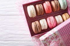 Beautiful macaroons in a pink gift box close-up on a table. Hori Stock Photography